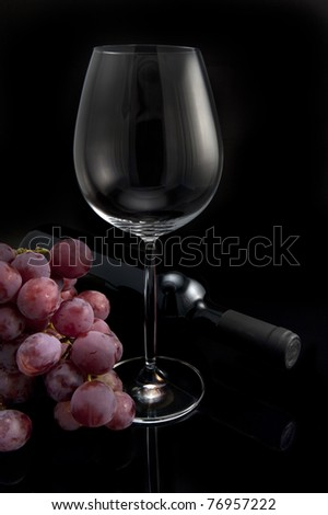 Glass, grapes and bottle of red wine on black background