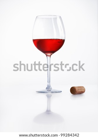 Glass half filled with red wine on a reflective white surface with a cork alongside at a party or celebration - stock photo