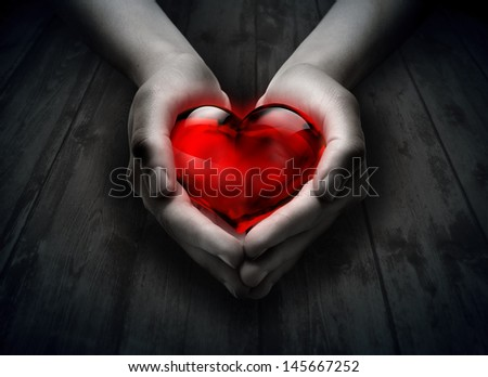 glass heart in the heart hand - stock photo