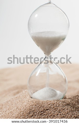 Glass hourglass standing in sand on a light background