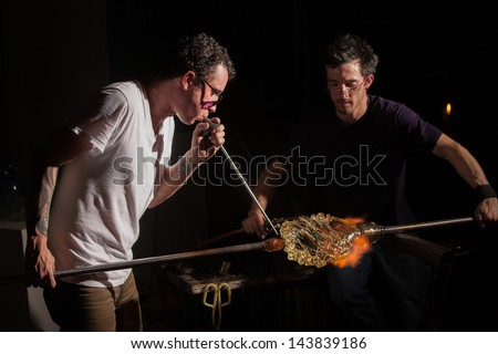 Glass industry artists working with blowpipe and blowtorch - stock photo