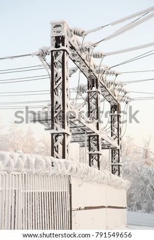Glass insulator on the power line. Insulator of electrical high-voltage lines winter