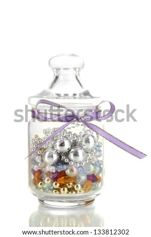 Glass jar containing various beads isolated on white - stock photo