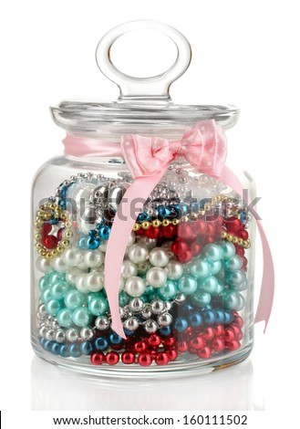 Glass jar containing various beads isolated on white