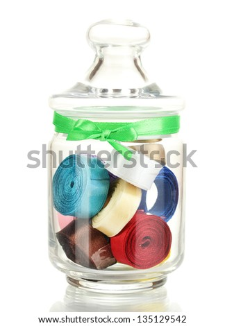 Glass jar containing various colored ribbons isolated on white - stock photo