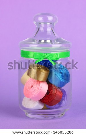 Glass jar containing various colored ribbons on lilac background - stock photo