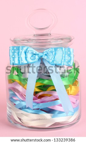 Glass jar containing various colored ribbons on pink background - stock photo