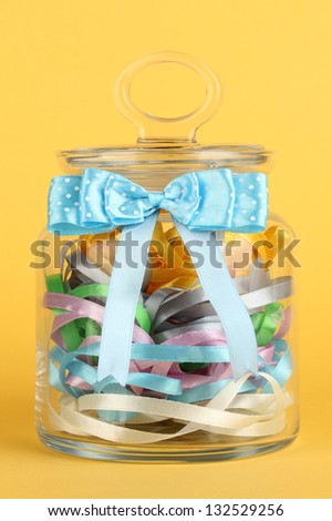 Glass jar containing various colored ribbons on yellow background - stock photo