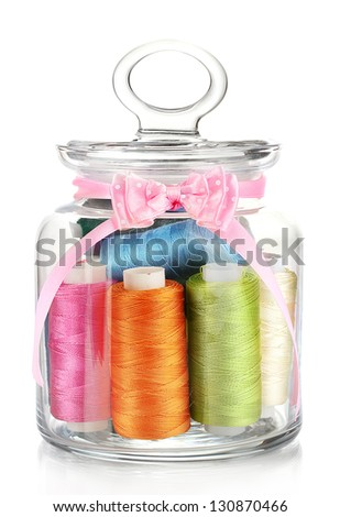 Glass jar containing various colored thread isolated on white - stock photo