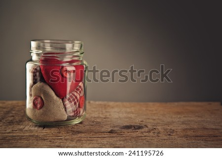 Glass Jar filled with collection of various cloth hearts - stock photo