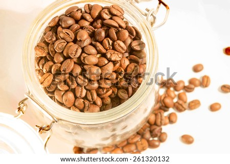Glass jar full of coffee beans isolated - stock photo