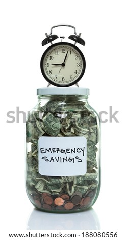 Glass jar full of money labeled with emergency savings with a clock sitting on top - stock photo