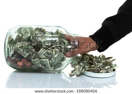 Glass jar full of money tipped over on its side spilling money with hand reaching in - stock photo