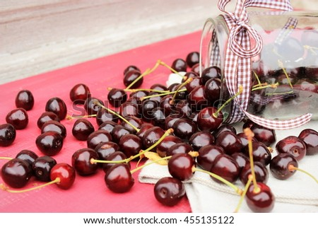 Glass jar full of ripe tasty black cherry with grey linen cloth on red wooden table. Composition with berries in bright color with rustic decor elements - stock photo