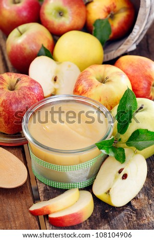 Glass jar of fresh apple sauce on an old wooden table with sliced fresh apples - stock photo