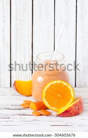 Glass jar of fresh homemade smoothie with orange, carrot and peach. - stock photo