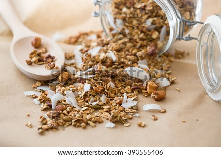 Glass jar of homemade organic granola with coconut and pecans on the baking paper background. Delicious breakfast cereal. Healthy muesli. - stock photo