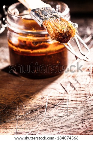 Glass jar of homemade spicy basting sauce and a brush on an old scored wooden chopping board in a rustic kitchen - stock photo