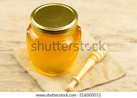glass jar of honey on jute fabric with drizzler on wooden background - stock photo