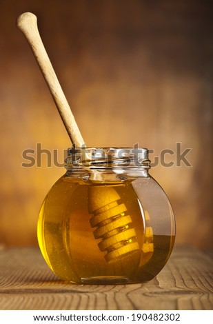 Glass jar of honey with wooden drizzler on a wooden background. - stock photo