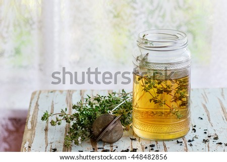 Glass jar of hot herbal tea with bunch of fresh thyme, served with vintage tea-strainer on old wooden stool with window at background. Rustic style, natural day light.