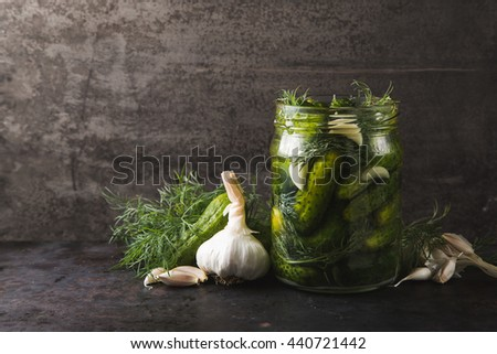 Glass jar of pickled gherkins with dill and garlic on dark metal grey rustic background, copy space