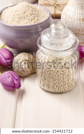 Glass jar of sea salt on white wooden table, tulip flowers in the background - stock photo