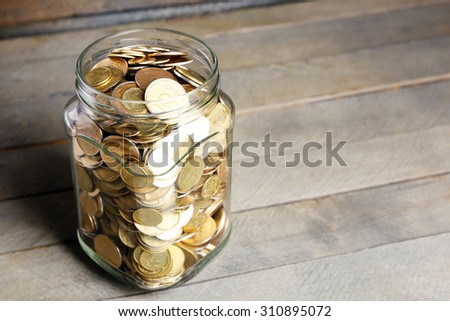 Glass jar with coins on wooden background - stock photo