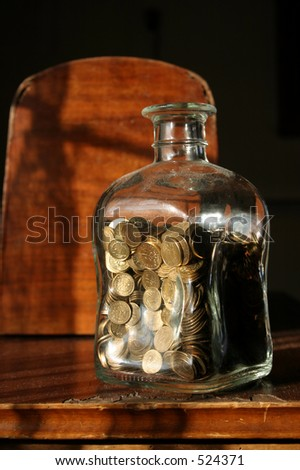 Glass jar with coins paced on a dark background