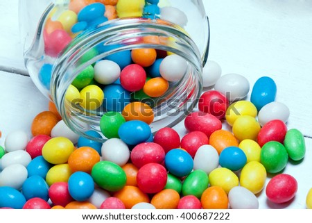 glass jar with colorful candy scattered on the painted  boards.festive background for your design.toned