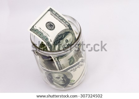 glass jar with dollars on a white background