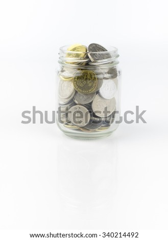 Glass jar with full of coins over white background - stock photo
