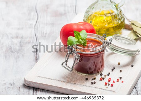 Glass jar with homemade classic spicy tomato pasta or pizza sauce. Italian healthy food on white wooden background. - stock photo