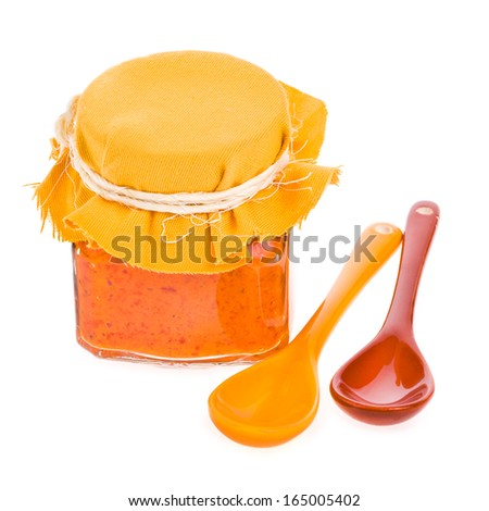 glass jar with paprika sauce, ceramic spoons isolated on white background - stock photo
