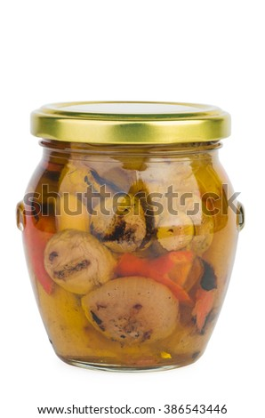 Glass jar with roasted vegetables in oil isolated on white background
