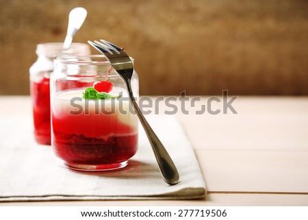 Glass jar with tasty panna cotta dessert on plate, on wooden table - stock photo