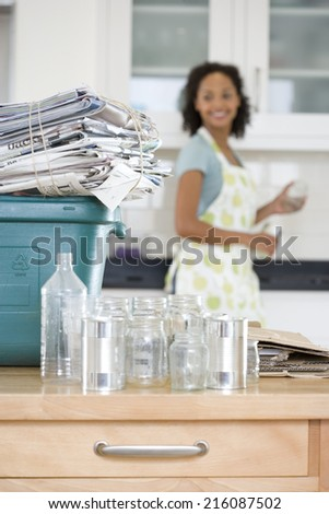 Glass jars and cans by recycling bin with newspapers in kitchen, woman in background - stock photo