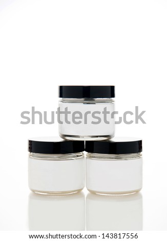 Glass Jars of Skin Care Product with White Labels on Background with Reflection - stock photo