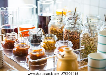 Glass jars with homemade jam, nuts and cereals - stock photo