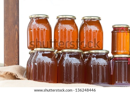 Glass jars with honey on a table isolated on white background