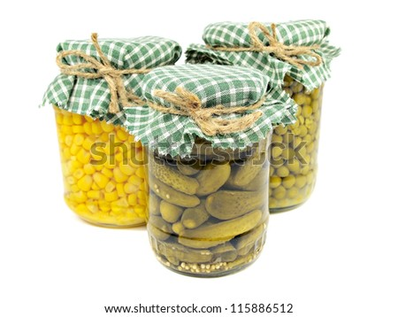 Glass jars with pickled cucumbers, canned green peas and sweet corn on a white background