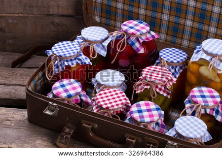 Glass jars with preservation in an old suitcase. Wooden shelves of old boards. - stock photo