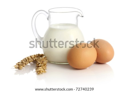 Glass jug with milk, wheat seeds and two eggs on white background - stock photo