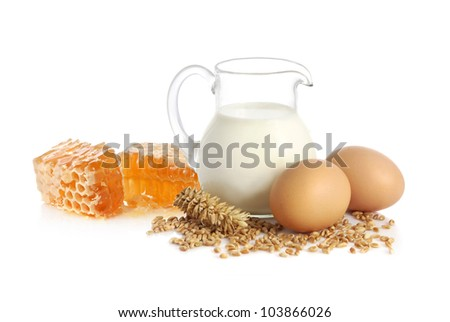 Glass jug with milk, wheat seeds, two eggs and yellow honeycomb on white background - stock photo
