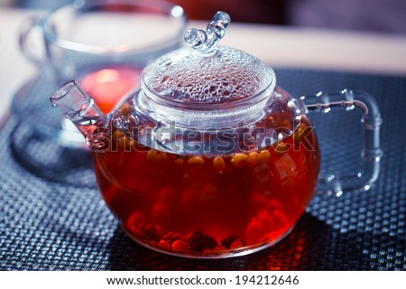 Glass kettle with red fruit tea - stock photo