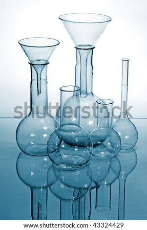 Glass laboratory equipment for science research in miroor - stock photo