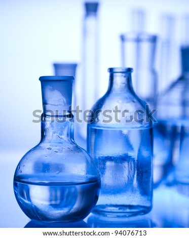 Glass laboratory equipment with blue background - stock photo
