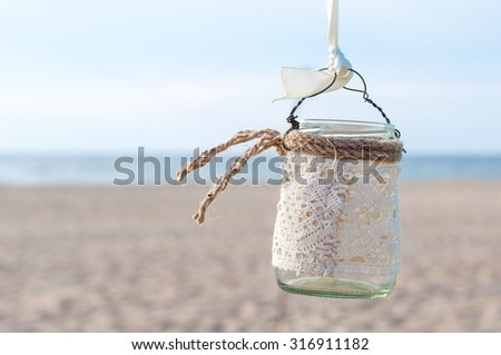 Glass lantern decorated with white lace hanging on wedding archway. Sea background. - stock photo