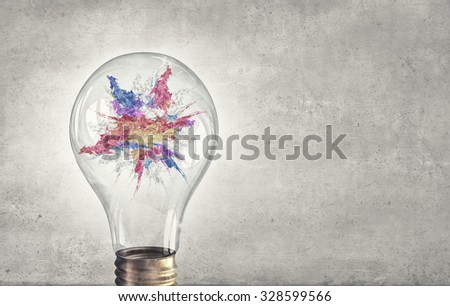Glass light bulb and colorful paint splashes inside - stock photo