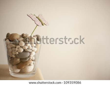 glass made vase with rounded stones inside ornament - stock photo